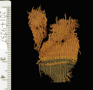 Tessuto tinto di rosso e blu, ritrovato a Timna. Il tessuto utilizzava i diversi colori pelo animale per creare i colori nero e arancio-marrone per le fasce decorative. Credit: Clara Amit, courtesy of the Israel Antiquities Authority