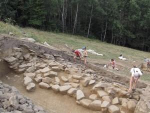 Vista della parte settentrionale degli scavi archeologici, alla metà di Agosto. Il muro conservatosi dalla Prima Età del Bronzo è visibile sullo spaccato del fossato, nel fondo del fossato una linea di rocce che forma lo strato più basso del muro. Foto di M.S. Przybyła.