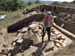 Misurazioni nel luogo dove nella parte esterna della base del muro conservatosi ci sono grandi pietre dal muro esterno che scivolarono per la discesa e a terra e si ribaltarono. Foto di M.S. Przybyła.