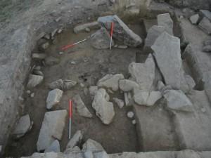 Vista delle lastre di pietra che segnano il passaggio che conduce all'interno dell'insediamento, sul fondo della fotografia uno dei blocchi dalla facciata esterna del muro. Foto di M.S. Przybyła.