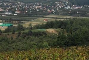 """Vista dell'area degli scavi archeologici sulla """"Collina di Zyndram"""" a Maszkowice, sullo sfondo una vista panoramica di Łącko. È facile vedere l'appiattimento artificiale della vetta e lo scosceso pendio orientale, che nasconde le fortificazioni in pietra dell'Età del Bronzo. Foto di A. Maślak."""