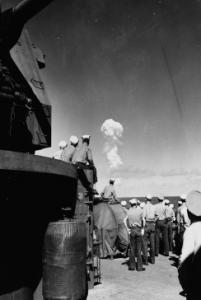 """Marinai che guardano l'esplosione dell'""""Able Test"""" a miglia di distanza, dal ponte della nave di supporto USS Fall River, 1 Luglio 1946 ©Naval History and Heritage Command"""